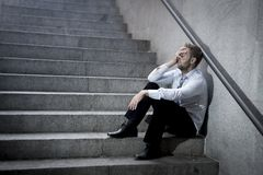 Gråta för affärsman som är borttappat i fördjupningssammanträde på gatabetongtrappa