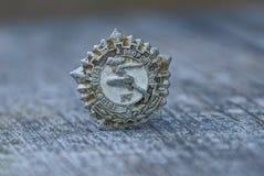 Grått gammalt sportsligt sovjetiskt emblem på trätabellen arkivbild