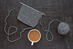 Grått handarbete och kaffe på svart bakgrund royaltyfri fotografi