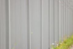 grått metallstaket i längden som en bakgrund och ett gräsplanblad Arkivbild