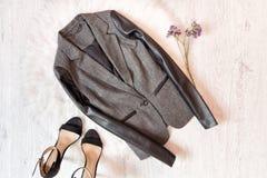 Grått omslag med en lädermuff, svarta skor, lösa blommor Trendigt begrepp på vit päls Royaltyfri Fotografi