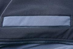 Grått svart bakgrundstyg av kläder med ett fack och en vinande arkivbild