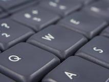 Grått tangentbord med fokusen på q och knappar och mjuk fokus Arkivbild