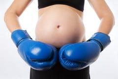 Grèves de femme enceinte dans des gants de boxe Photographie stock libre de droits
