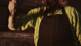 Grèves de forgeron avec un marteau sur un objet en métal sur l'enclume Plan rapproché de son visage H banque de vidéos