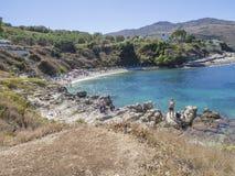 Grécia, Corfu, Kassiopi 28 de setembro de 2018: Opinião a praia branca da areia de Bataria com sunbeds azuis e os povos do turist imagens de stock royalty free