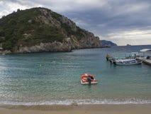 Grécia, Corfu, Paleokastritsa, o 26 de setembro de 2018: barcos vermelhos do barco a motor e de turista que estacionam no cais na fotos de stock
