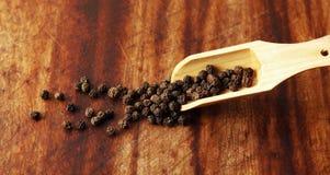 Grões da pimenta e colher de madeira Foto de Stock