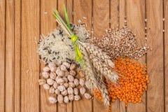 Grões do arroz, das lentilhas, dos trigos mouriscos e dos grãos-de-bico com orelhas do trigo Fotografia de Stock Royalty Free