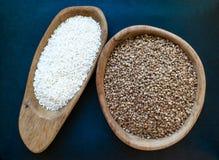 Grões do arroz e do trigo mourisco em uns frascos de madeira colocados na superfície azul profunda do fundo imagens de stock royalty free