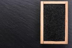 Grões do cominhos e do óleo pretos no fundo rústico imagem de stock