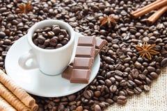 Grões fritadas do café com um copo em uma bandeja de prata com chocolate e biscoitos em feijões de uma xícara de café imagem de stock