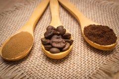 Grões, terra e café instantâneo com a colher de madeira na lona da juta Foto de Stock Royalty Free