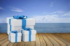 Größe drei der Geschenkbox des weißen Quadrats mit blauem Band setzte an Holztisch gegen Seeansicht kopieren Sie Raum für addiere Stockfoto