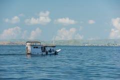 Größtenteils ein Boot, das auf das ruhige Wasser nahe dem Ozean smoothe schwimmt Lizenzfreie Stockfotos