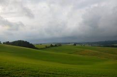 Grön äng med dramatisk himmel Arkivbild