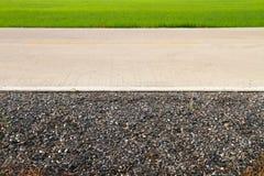 Grön äng med träd och asfaltvägen Arkivbilder