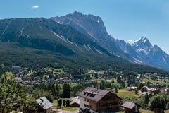 Grön äng och typiska hus bland berglandskap i sommar Tid Royaltyfria Bilder