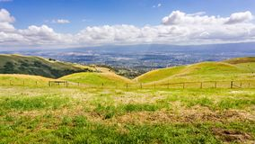 Grön äng på kullarna av södra San Francisco Bay område; San Jose som är synligt i bakgrunden; Kalifornien arkivfoto