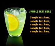 Grön alkoholcoctail med citronskivan som isoleras på svart arkivbild