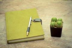 Grön anteckningsbok-, penn- och kaktuskruka på träskrivbordet - tappningstil Arkivbild