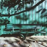Grön bänk mot ett grönt staket Royaltyfri Bild