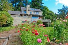 Grön backayrdträdgård med trevliga blommor Royaltyfri Bild