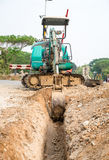 Grön backhoe som muddrar jord Royaltyfri Foto