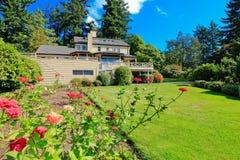 Grön bakgårdträdgård med trevliga blommor royaltyfria bilder