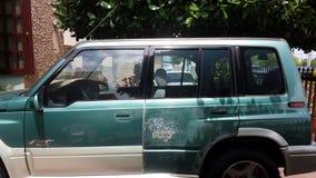 Grön bil med hål och skada arkivbild