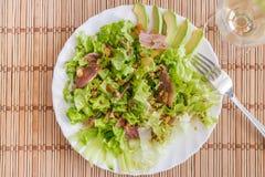 Grön blandningsalladplatta med avokadot, prosciuttoen, russin och pecannötter över matt bambu Fotografering för Bildbyråer