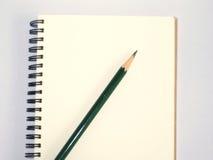 Grön blyertspenna på en anteckningsbok arkivfoto