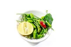 Grön chili och gul limefruktlamon på den vita bakgrunden Fotografering för Bildbyråer