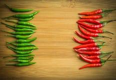 Grön chilipeppar på peppar för vänster sida och för röd chili på rätsida av att hugga av kvarteret Arkivbilder
