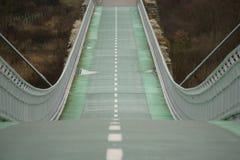 Grön cykelbro till för himmel kullen ner Arkivbild