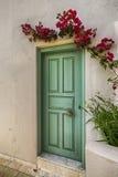 Grön dörr i den vita eallen med små lpurpleflouers Arkivbilder