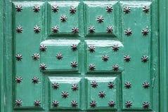 Grön dörr med prydnadar i form av den svart stjärnan, bakgrund Royaltyfria Foton
