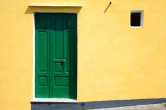 Grön dörr på den gula väggen Royaltyfri Bild