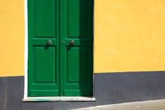 Grön dörr på den gula väggen Royaltyfria Foton