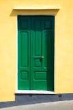 Grön dörr på den gula väggen Fotografering för Bildbyråer