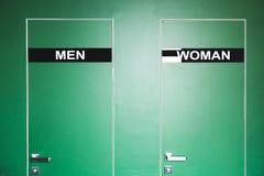 Grön dörr till toaletten med den inskriftmannen och kvinnlign Arkivbilder