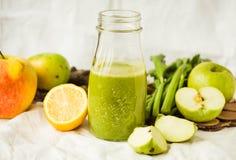 Grön detoxfruktsaft med äpplet, grönkål, citronen och selleri royaltyfria foton