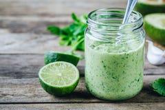 Grön dressing med avokadot, limefrukt och koriander i en glass krus arkivbild