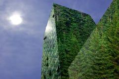 Grön energi i staden: modern byggnad som täckas med skogen Arkivbild
