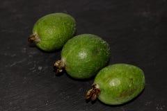Grön exotisk fruktfeijoa på en svart bakgrund arkivbild