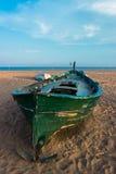 Grön fiskebåt på stranden och den blåa himlen Arkivbild
