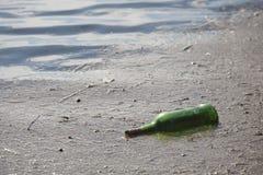 Grön flaska i ett damm, en förorening och skräpa ner fotografering för bildbyråer