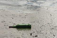 Grön flaska i ett damm, en förorening och skräpa ner Förkylning tonar royaltyfri fotografi