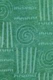 Grön frottéhandduk med den geometriska och spiral modellen Royaltyfri Bild