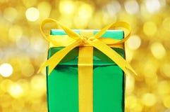 Grön gåva på röd oskarp lampabakgrund. royaltyfria foton